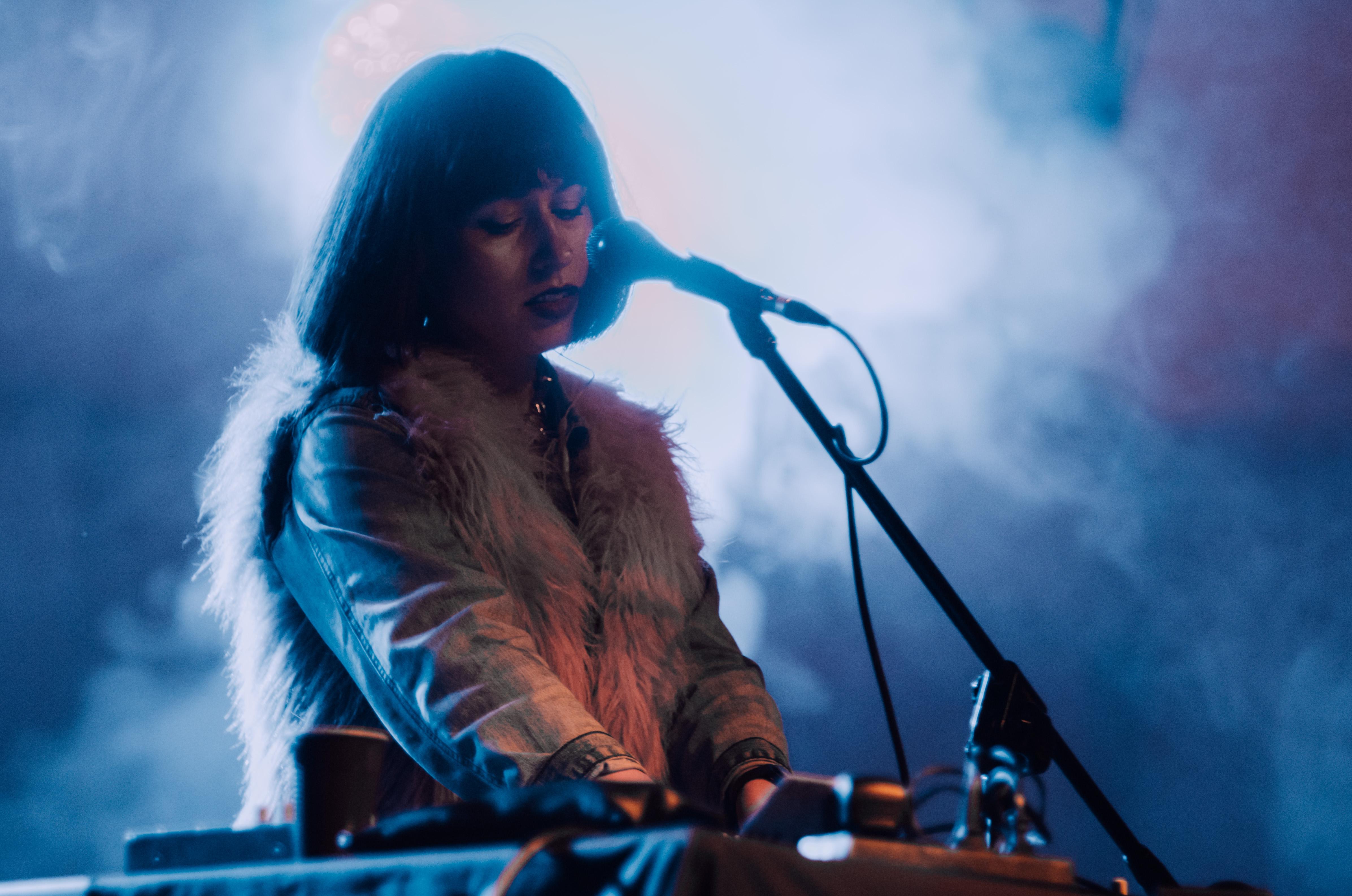 [Na scenie Natalia Kunitskaya. Koncert Mustelide. Kobieta wytwarza dźwięki na mikserze. Przed sobą ma mikrofon umieszczony na statywie. Oczy artystki są przymknięte, jej twarz jest pełna natchnienia.]
