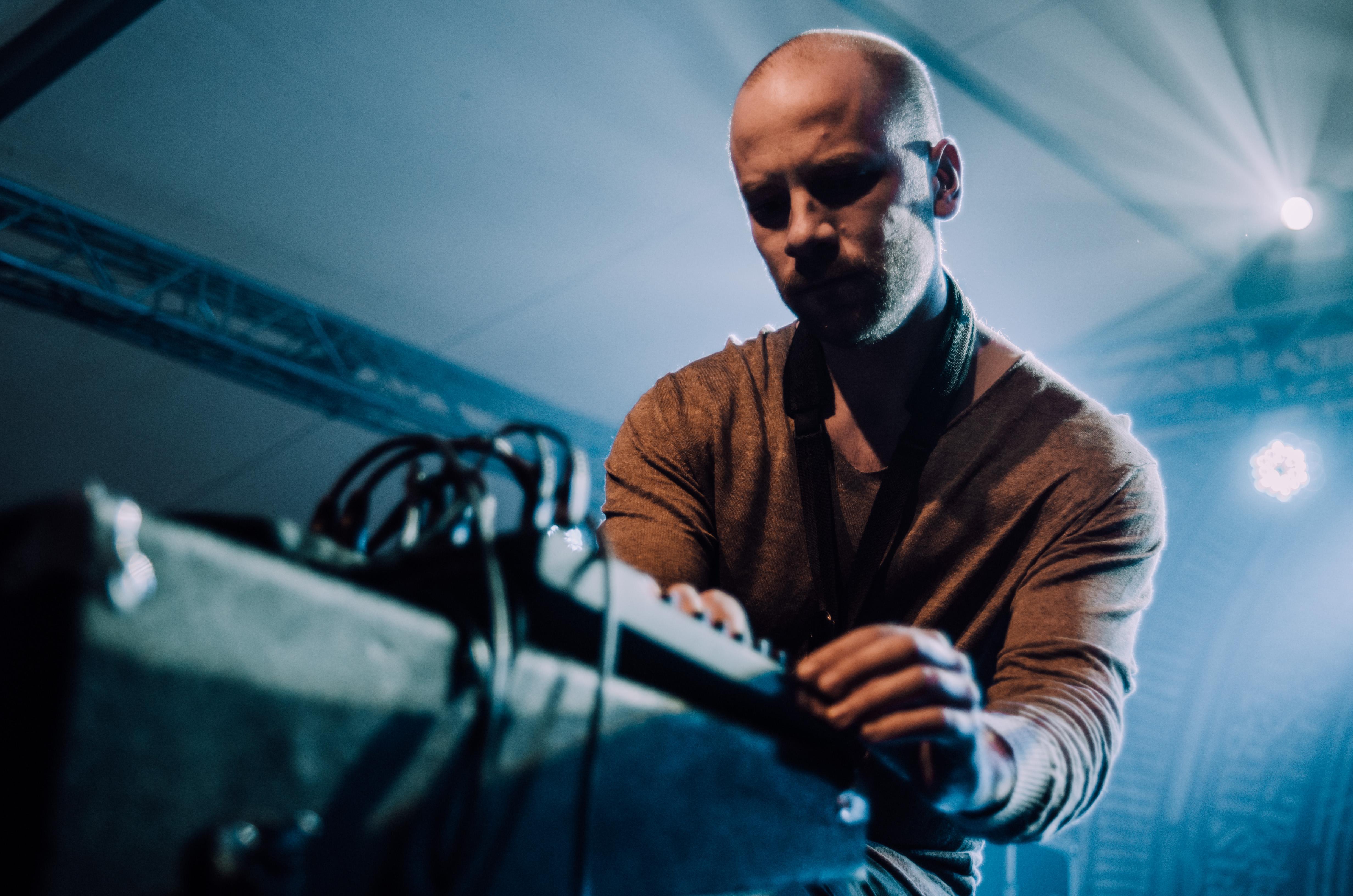 [Zbliżenie na mężczyznę skupionego na wytwarzaniu dźwięku na mikserze. W tle oświetlenie niebieskie.]