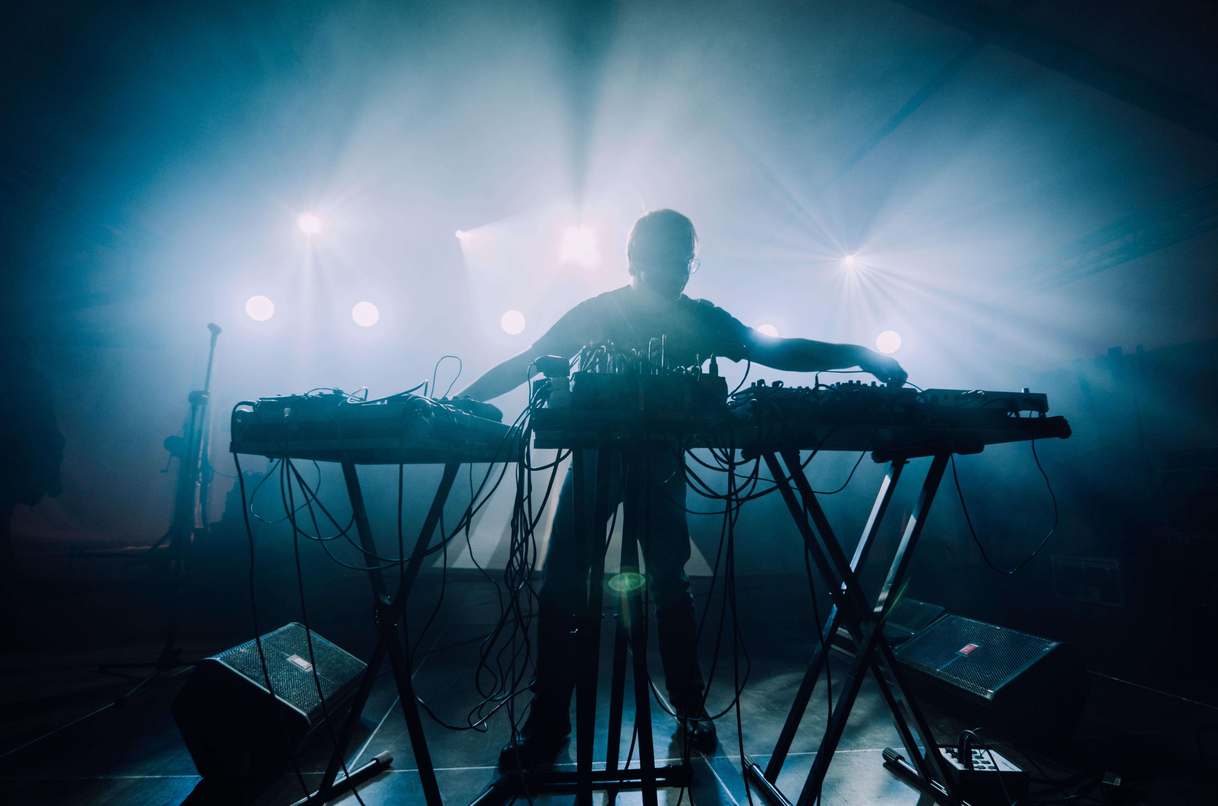 [Na zdjęciu widoczna sylwetka mężczyzny tworzącego dźwięki na konsoli. Mocne, niebieskie światła za jego plecami.]