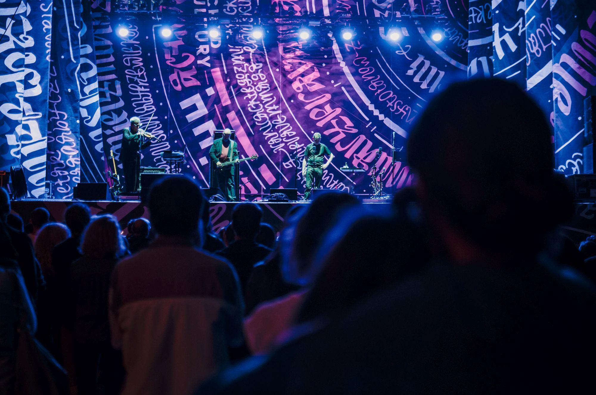 [Koncert na Scenie Głównej. Mężczyzna grający na skrzypcach, gitarzysta oraz wokalista. W tle scenografia  logo festiwalu Inne Brzmienia. Pod sceną zebrana publiczność.]