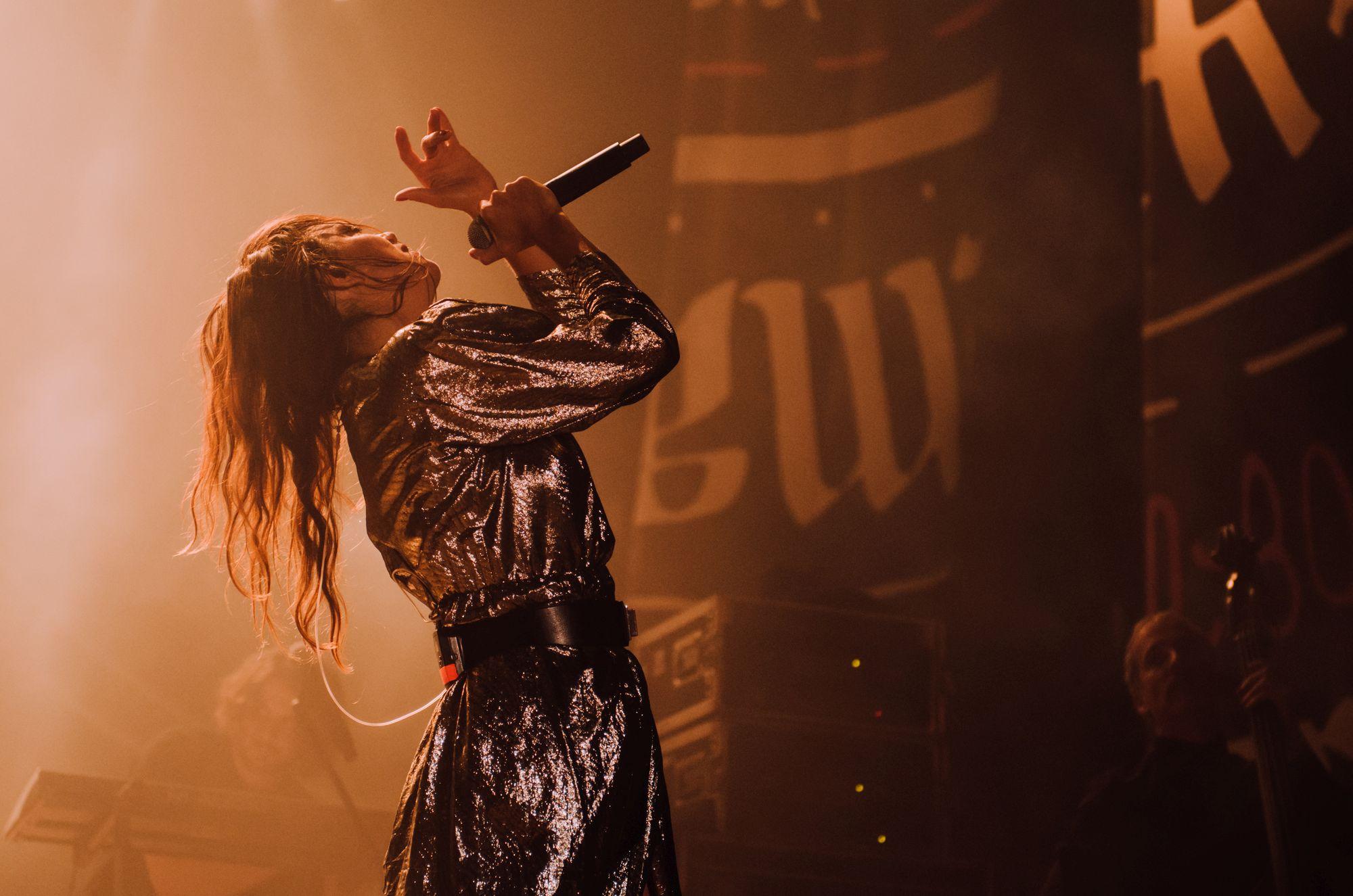 [Zdjęcie z koncertu. Zbliżenie na śpiewającą kobietę w pełnej poruszenia pozycji. Widok z boku. Ciepłe, żółte oświetlenie.]