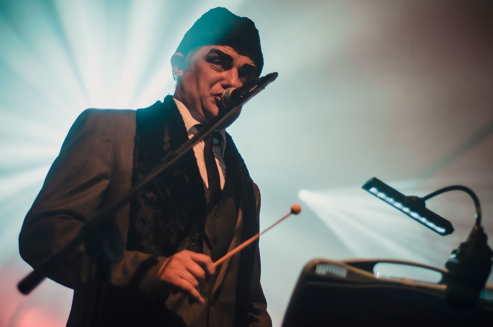 [Mężczyzna z zespołu Gromyka śpiewa do mikrofonu. Ma mocno pomalowane na ciemno brwi i czapkę na głowie. W ręku trzyma pałeczkę. W tle przebija jasne światło.]
