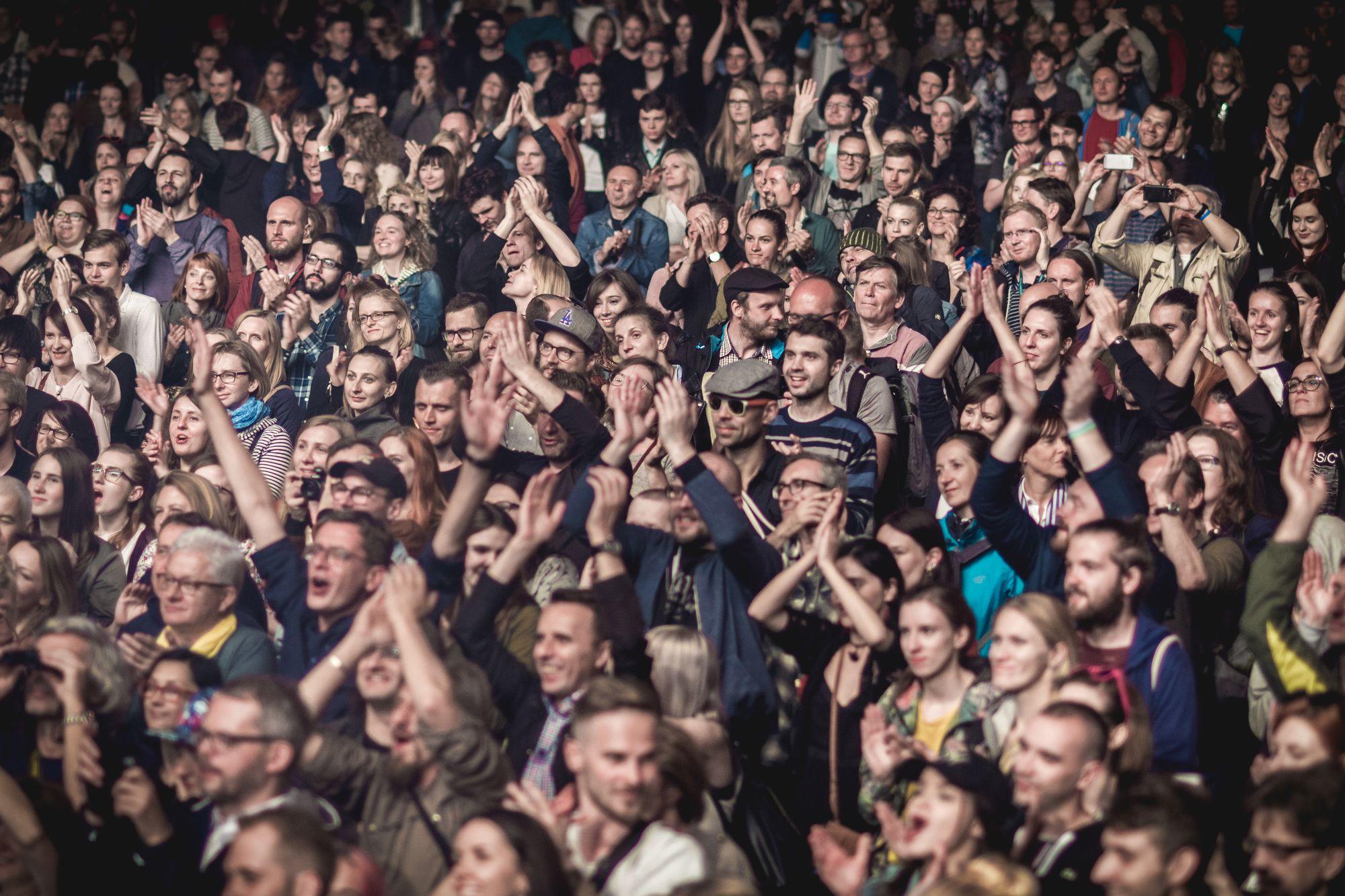 [Zdjęcie przedstawia rozentuzjazmowaną publiczność podczas koncertu. Widać, że wszyscy dobrze się bawią. Oświetla ich jasne światło.]