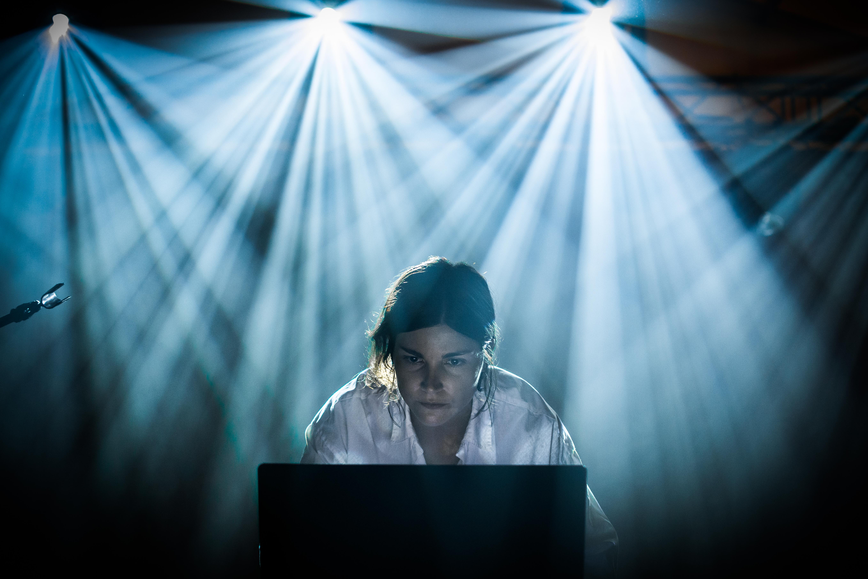 [Kobieta w białej koszuli nachylona nad komputerem, tworzy muzykę. Stoi na scenie w świetle reflektorów]