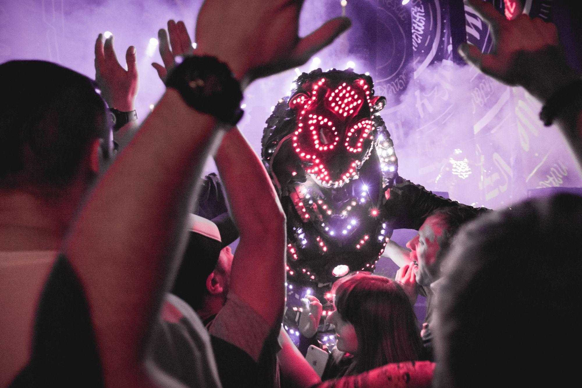 [Zdjęcie z perspektywy roztańczonej publiczności podczas koncertu Juno Reactor i Mutant Theatre. Jeden z członków zespołu ubrany w kostium podświetlony kolorowymi światełkami nachyla się w stronę koncertowiczów.]