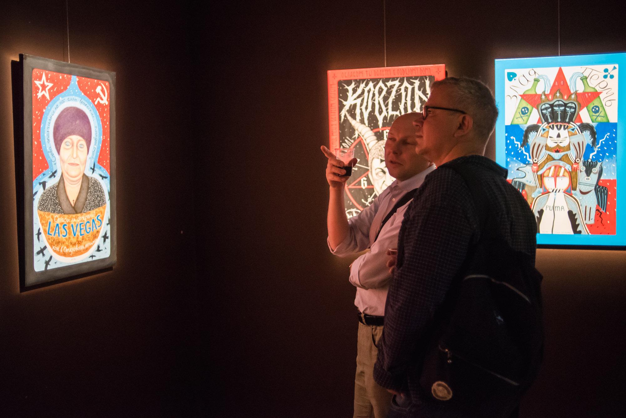 """[Wystawa Orient Station - """"Baśnie rosyjskiego świata"""" i """"Ukraińskie sny"""". Dwóch mężczyzn wpatruje się w zawieszone eksponaty. Jeden z nich pokazuje palcem wskazującym na jeden z obrazów i widać, że coś tłumaczy swojemu towarzyszowi. Ten słucha go z ciekawością.]"""