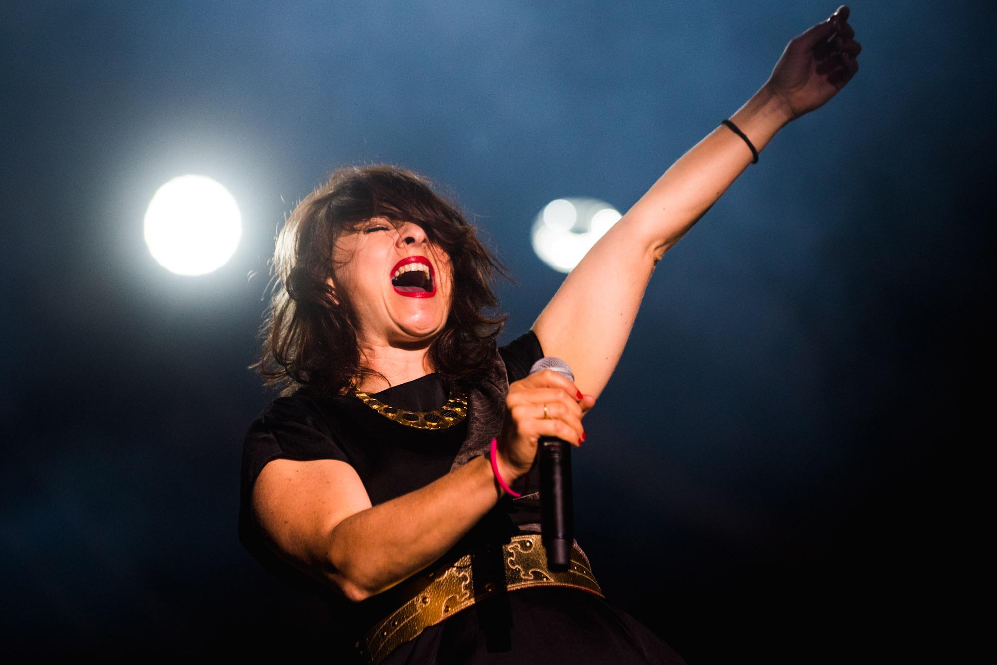 [Zbliżenie na śpiewającą kobietę. Powieki ma mocno ściśnięte, usta szeroko otwarte. Widać ogromne zaangażowanie na jej twarzy. W jednej ręce trzyma mikrofon, drugą ma uniesioną do góry.]