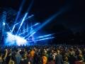 [Zdjęcie z koncertu. Zdjęcie z boku na Scenę Główną całą we mgle i rozentuzjazmowaną publiczność. Niebieskie strumienie światła ze sceny wystrzeliwują na koncertowiczów i ciemne niebo.]