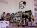 """[Zdjęcie przedstawia wystawę """"Peekaboo"""" w Warsztatach Kultury w Lublinie. Na zdjęciu cztery osoby siedzące na dużych siedziskach przeglądają książki. Na białych ścianach nad nimi widoczne logo wystawy: kształt wertowanej książki z napisem na okładce: Peek-a-boo, oraz wyglądający zza nich graficzny kształt twarzy. Odbiorcy wystawy siedzą przy czarnych półkach na których wystawione są książki.]"""