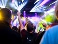 [Zdjęcie z koncertu zrobione z perspektywy publiczności. Widoczne są sylwetki mężczyzn i kobiet. Ręce mają podniesione do góry. Powyżej widoczne są światła na scenie oraz elementy konstrukcji scenicznej.]