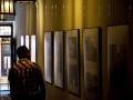[Zdjęcie przedstawia wystawę fotografii Romualdasa Požerskisa - Litewskie Stare Miasta. Na białej ścianie umocowane na przezroczystych żyłkach wiszą zdjęcia w ramkach. Ogląda je mężczyzna stojący tyłem do obiektywu. Ma ciemne włosy i koszulę w kratkę. W tle widać lekko rozmazane wejście do kamienicy.]