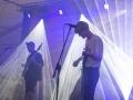 [Zdjęcie z koncertu Garbanotas przedstawia dwóch mężczyzn grających na gitarach. Przed każdym z nich stoi statyw z umieszczonym na nim mikrofonem. Oświetleni są fioletowym światłem.]