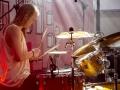 [Zdjęcie z koncertu zespołu Garbanotas. Mężczyzna w długich blond włosach i białej koszulce na ramiączkach gra na perkusji. W ręku trzyma pałeczki. W tle widoczne jest logo festiwalu Wschód Kultury - Inne Brzmienia.]