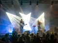 [Zdjęcie z koncertu zespołu Wrekmeister Harmonies. Na scenie mężczyzna w długich blond włosach gra na gitarze i śpiewa do mikrofonu umieszczonego na statywie. Obok kobieta w ciemnych włosach gra na skrzypcach. Poniżej kadru widoczne są sylwetki osób siedzących na widowni.]