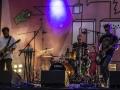 [Zdjęcie z koncertu zespołu Way Station. Na scenie dwóch gitarzystów oraz perkusista. W stronę każdego z artystów skierowane są mikrofony umieszczone na statywach. W tle widać różowe logo festiwalu Wschód Kultury - Inne Brzmienia]