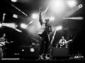 """[Zdjęcie czarno-białe. Scena koncertowa. Na środku muzyk: Lee """"Scratch"""" Perry w scenicznej odsłonie, w tle reszta zespołu]"""