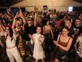 [Zdjęcie z koncertu pod namiotem. Ujęcie na publiczność. Grupa ludzi w różnym wieku, kobiet i mężczyzn. Część osób uśmiecha się szeroko i podnosi ręce do góry. Część wpatrzona jest ze skupieniem w kierunku sceny.]