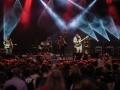 [Frontman zespołu Lee Scrach Perry, w błyszczącej marynarce stoi na środku sceny i macha do licznie zgromadzonej publiczności. W tle oświetlony światłem reflektorów zespół. ]