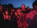 [Zdjęcie z koncertu przedstawia publiczność. Zbliżenie na uśmiechniętą czwórkę osób - trzy kobiety i dwóch mężczyzn. Oświetleni są różowym światłem ze sceny. Ponad nimi widać wierzchołki drzew i wieczorne niebo. Dookoła nich widać lekko rozmazane sylwetki innych osób z publiczności.]