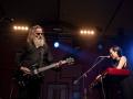 [Zdjęcie z koncertu zespołu Wrekmeister Harmonies. Mężczyzna w siwych, długich, rozpuszczonych włosach i siwej brodzie gra na gitarze. Ubrany jest cały na czarno. Po jego lewej stronie młoda kobieta w czarnych włosach i czarnej sukience gra na keyboardzie i śpiewa do mikrofonu. W tle widać różowe logo festiwalu Wschód Kultury - Inne Brzmienia.]