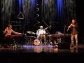 [Trójka muzyków na scenie, na środku perkusjonista z lewej strony muzyk przy konsoli z prawej mężczyzna z instrumentem dętym. Na scenę pada ciepłe światło]