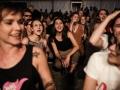 [Zdjęcie z koncertu przedstawia publiczność. Na pierwszym planie dwie młode kobiety wpatrzone są w kierunku sceny. Na ich twarzach wymalowana jest radość. Śpiewają razem a artystami. Dookoła widać lekko rozmazane sylwetki innych osób siedząch na publiczności.]