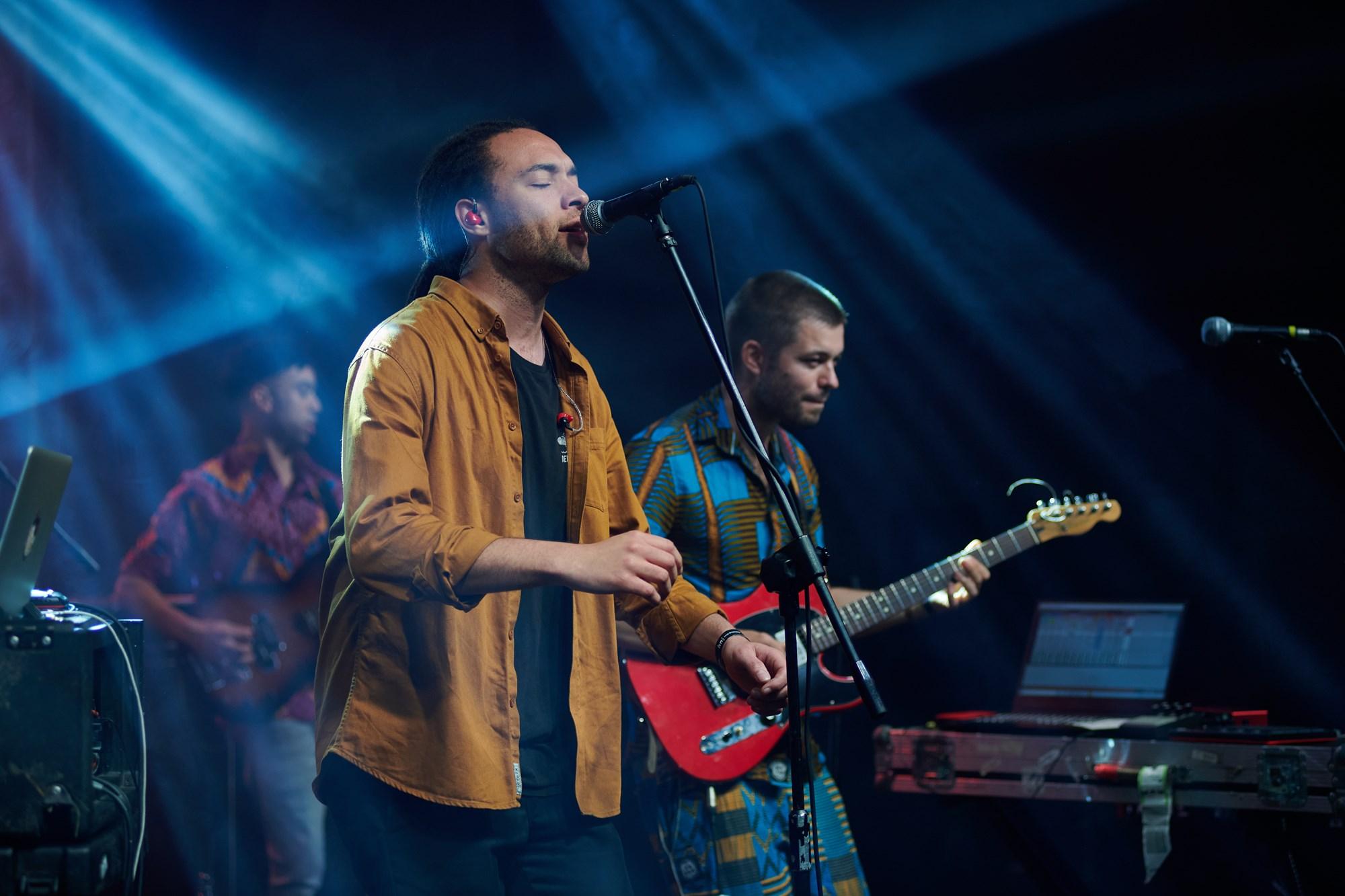 [Zdjęcie z koncertu Nubiyan Twist. Na pierwszym planie wokalista śpiewający do mikrofonu, w dredach i musztardowej koszuli, na drugim planie gitarzyści.]