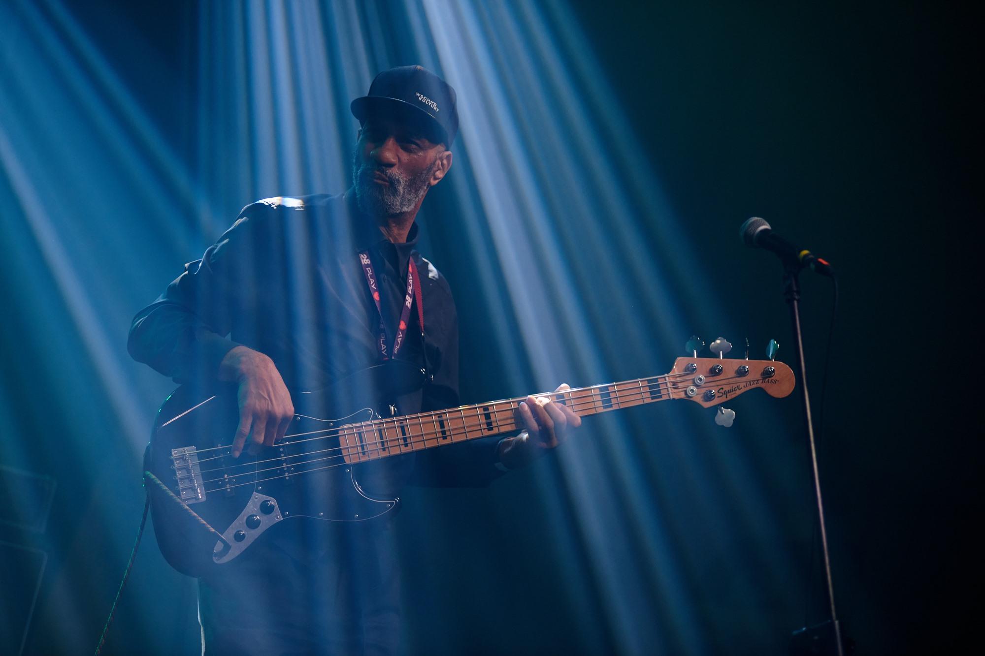 [Zdjęcie z koncertu Ayoub Houmanna & Nomads Moods. Mężczyzna w czarnej czapce z daszkiem gra na gitarze elektrycznej. Stoi w niebieskim oświetleniu.]