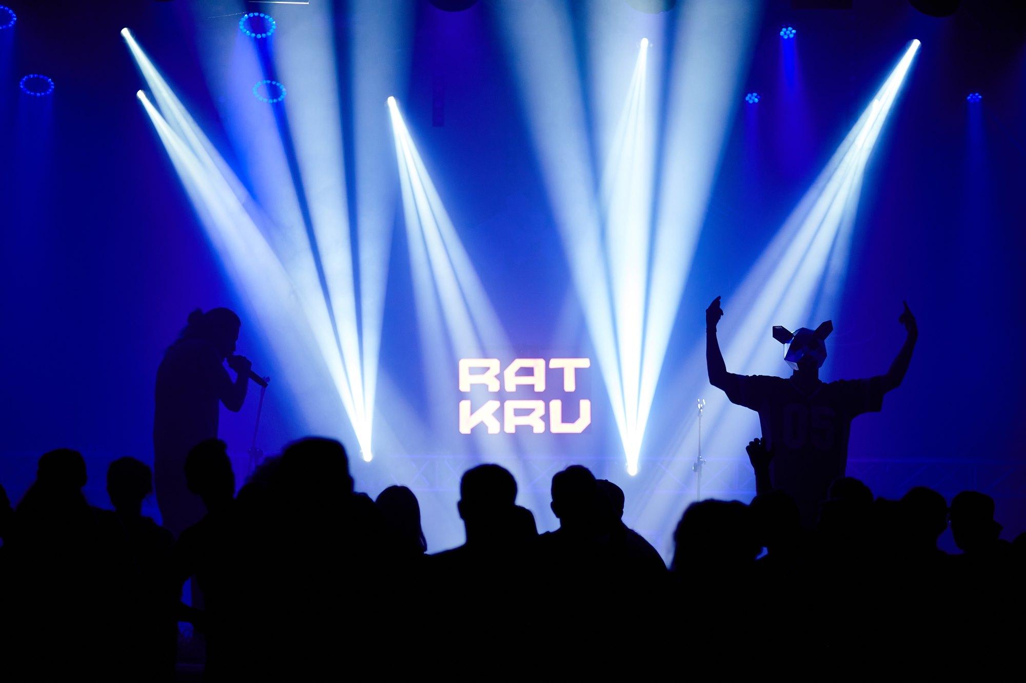 [Zdjęcie z koncertu przedstawia scenę z wyświetlonym na środku napisem nazwy zespołu - Rat Kru. Po obydwu stronach napisu duet Rat Kru - dwóch mężczyzn, jeden w masce szczura. Na drugim planie sylwetki osób na widowni.]