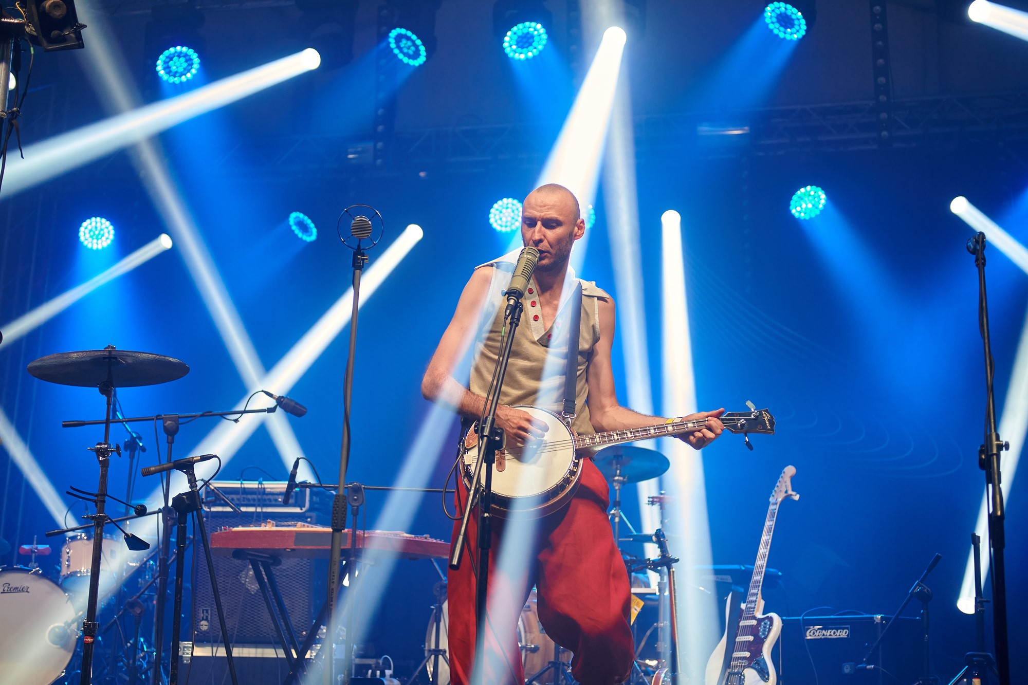 [Zdjęcie z koncertu zespołu Hańba. Zdjęcie przedstawia mężczyznę w jasnej koszuli i czerwonych spodniach grającego na Banjo stojącego przy mikrofonie]