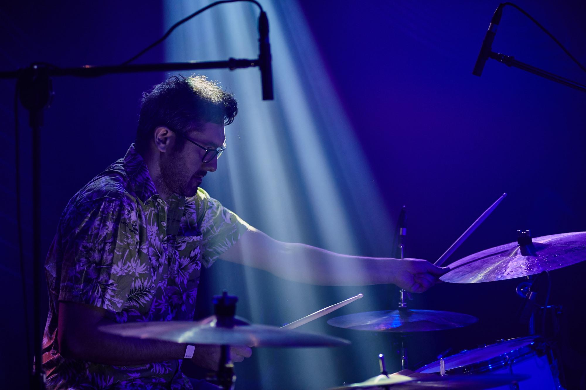 [Zdjęcie z koncertu zespołu Javva przedstawia mężczyznę w okularach i koszuli grającego na perkusji.]