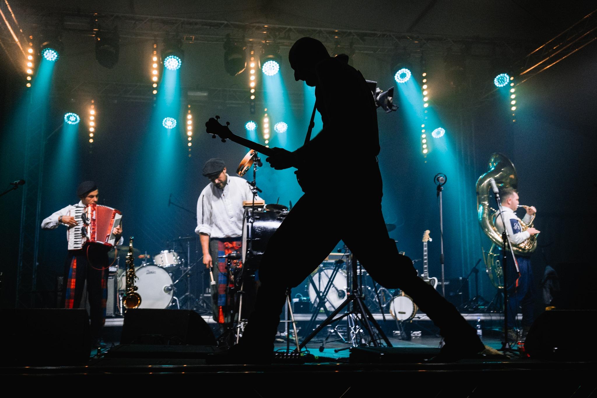 [Zdjęcie z koncertu zespołu Hańba przedstawia ciemną sylwetkę mężczyzny grającego na gitarze. W tle trzech mężczyzn w beretach, białych koszulach i kolorowych spodniach grających na instrumentach muzycznych.]