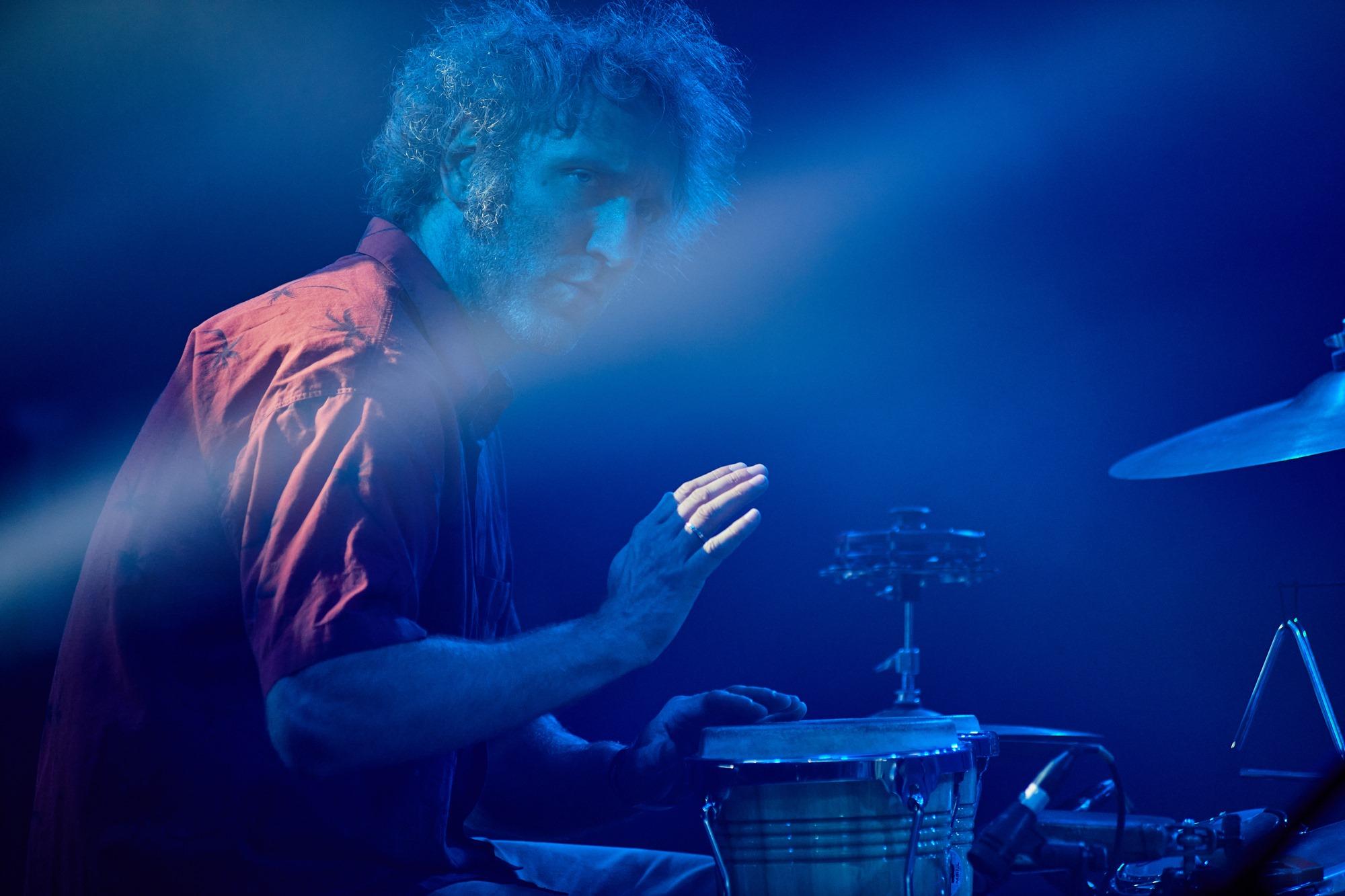 [Zdjęcie z koncertu przedstawia mężczyznę w czerwonej koszuli grającego na bębnie]