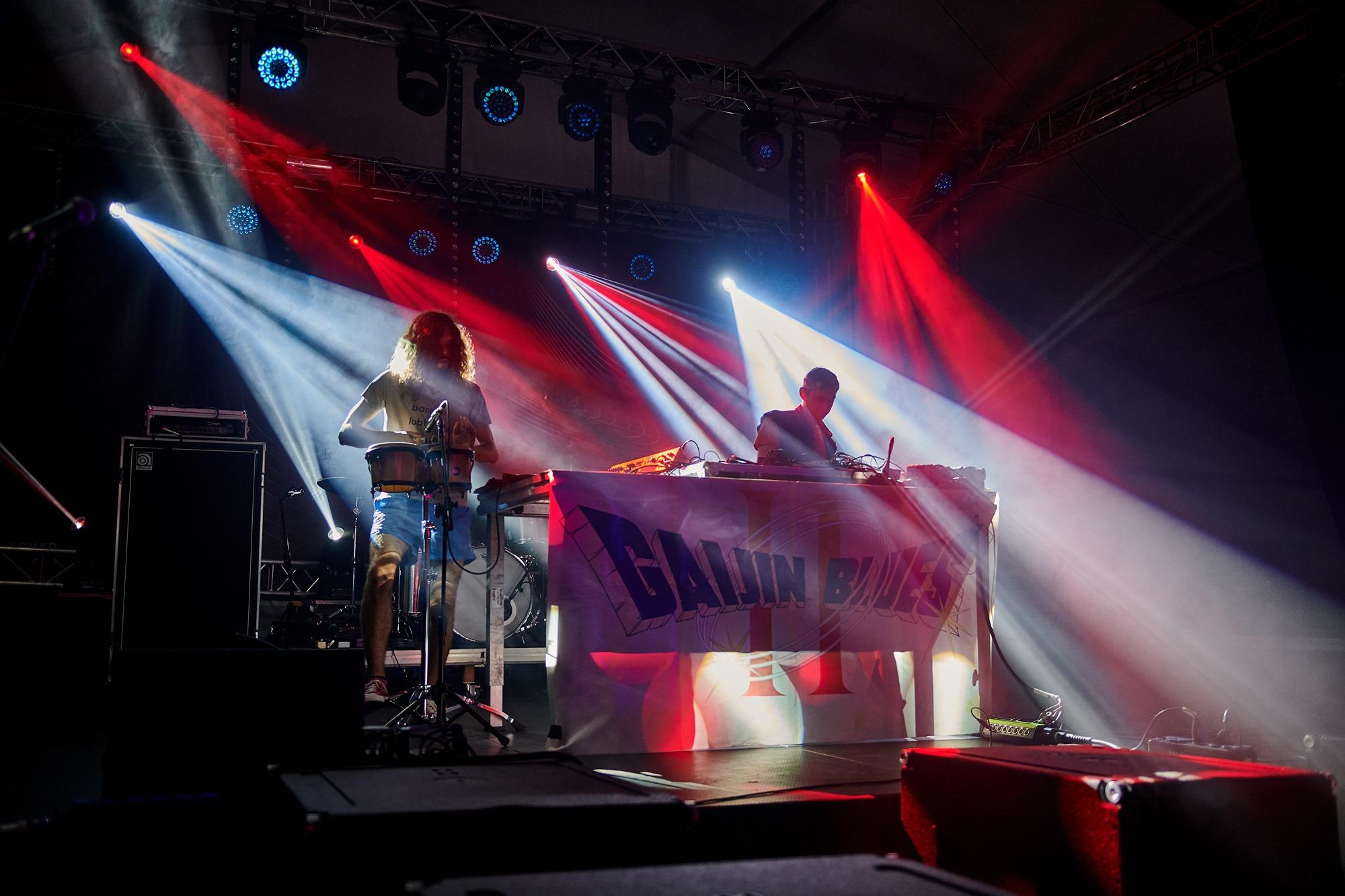 [Zdjęcie z koncertu przedstawia elektroniczny duet Gaijin Blues. Mężczyzna w długich włosach z lewej strony gra na bębnach. Mężczyzna z prawej strony tworzy dźwięki na mikserze.]