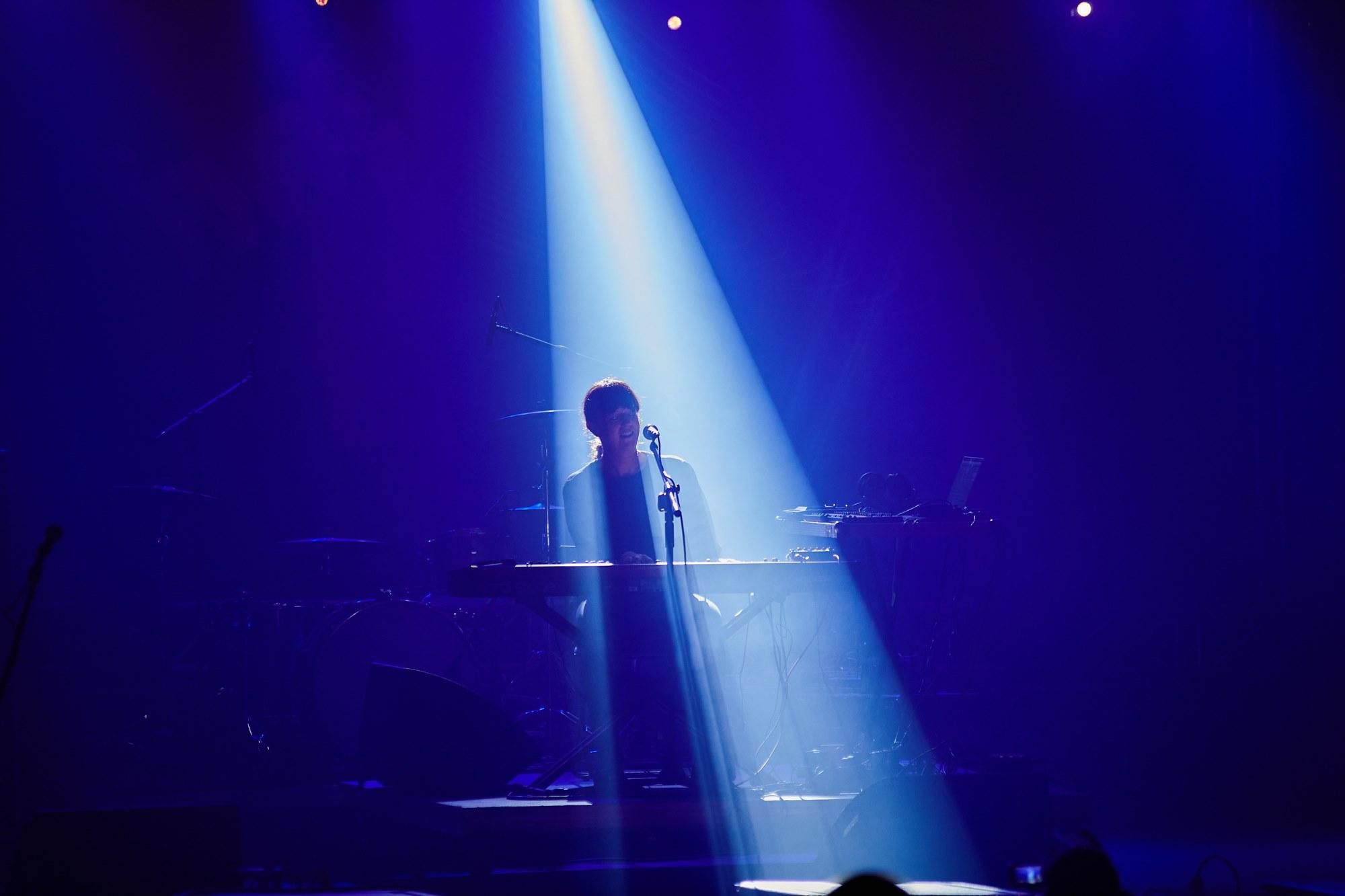 [Zdjęcie z koncertu Barbary Morgenstern przedstawia kobietę oświetloną niebieskim światłem. Kobieta siedzi przy mikrofonie i gra na keyboardzie.]