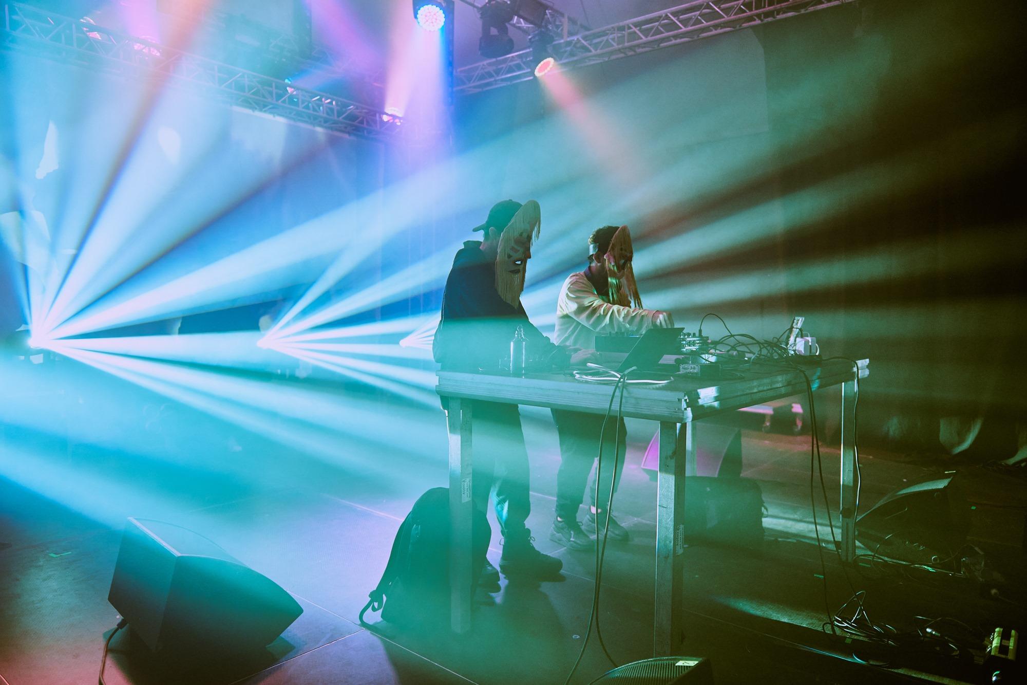 [Zdjęcie z koncertu Dengue Dengue Dengue przedstawia dwóch mężczyzn w maskach. Mężczyźni tworzą dźwięki za pomocą miksera. Oświetleni są zielonym i różowym światłem.]