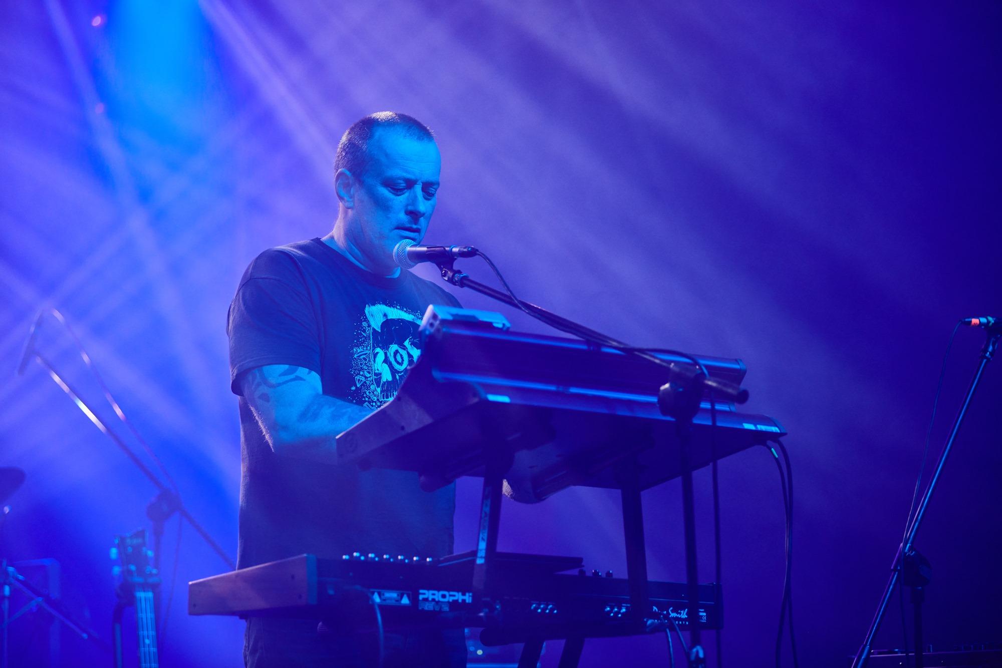 [Zdjęcie z koncertu zespołu MU. Na zdjęciu lider zespołu Tymon Tymański. Na tle niebieskiego oświetlenia stoi mężczyzna przy mikrofonie, grający na keyboardzie.]