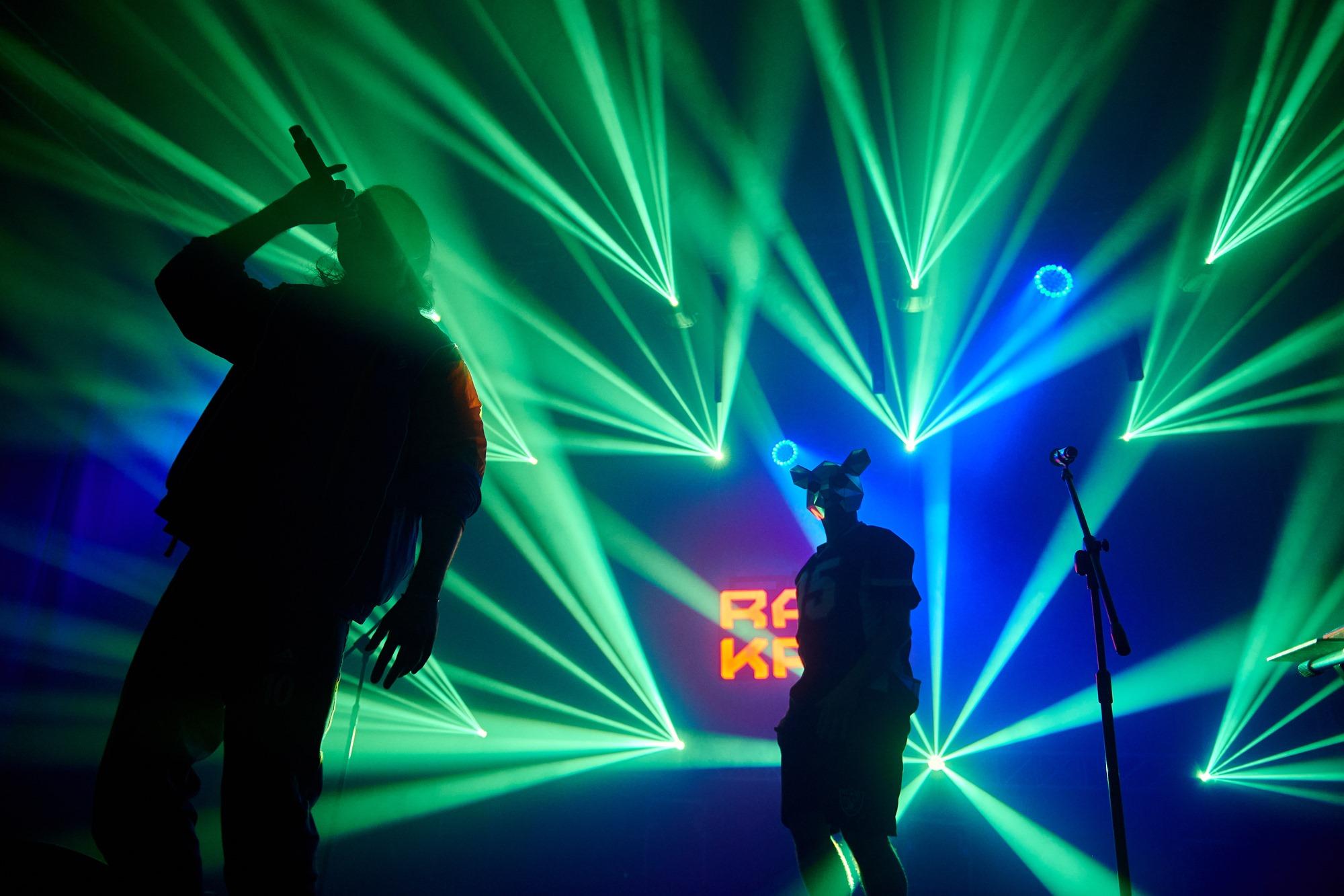 [Zdjęcie z koncertu przedstawiające duet Rat Kru - dwóch mężczyzn. Jeden z nich trzyma mikrofon przy ustach, drugi ma założoną na twarzy maskę szczura. Stoją na scenie oświetleni zielonymi światłami.]