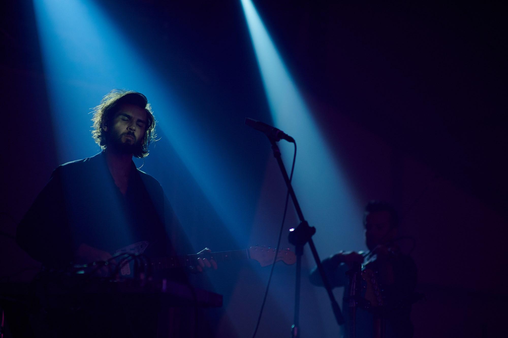 [Zdjęcie z koncertu Daniela Spaleniaka. Na pierwszym planie mężczyzna grający na gitarze. Na drugim planie mężczyzna grający na skrzypcach.]