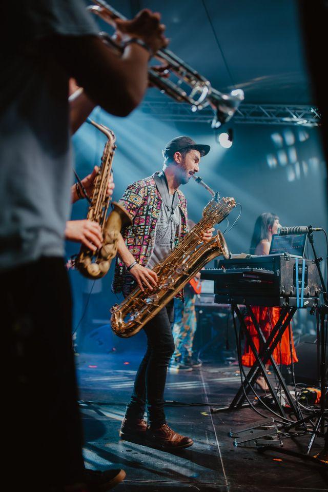 [Zdjęcie z koncertu Nubiyan Twist. Scena oświetlona na niebiesko. W centrum zdjęcia mężczyzna w czapce z daszkiem gra na saksofonie. Obok niego stoją sprzęty muzyczne. Na pierwszym planie widoczne są trabka i saksofon na których grają dwie osoby z zespołu. W tle widoczna jest kobieta w ciemnych włosach i czerwonej sukience śpiewająca do mikrofonu.]