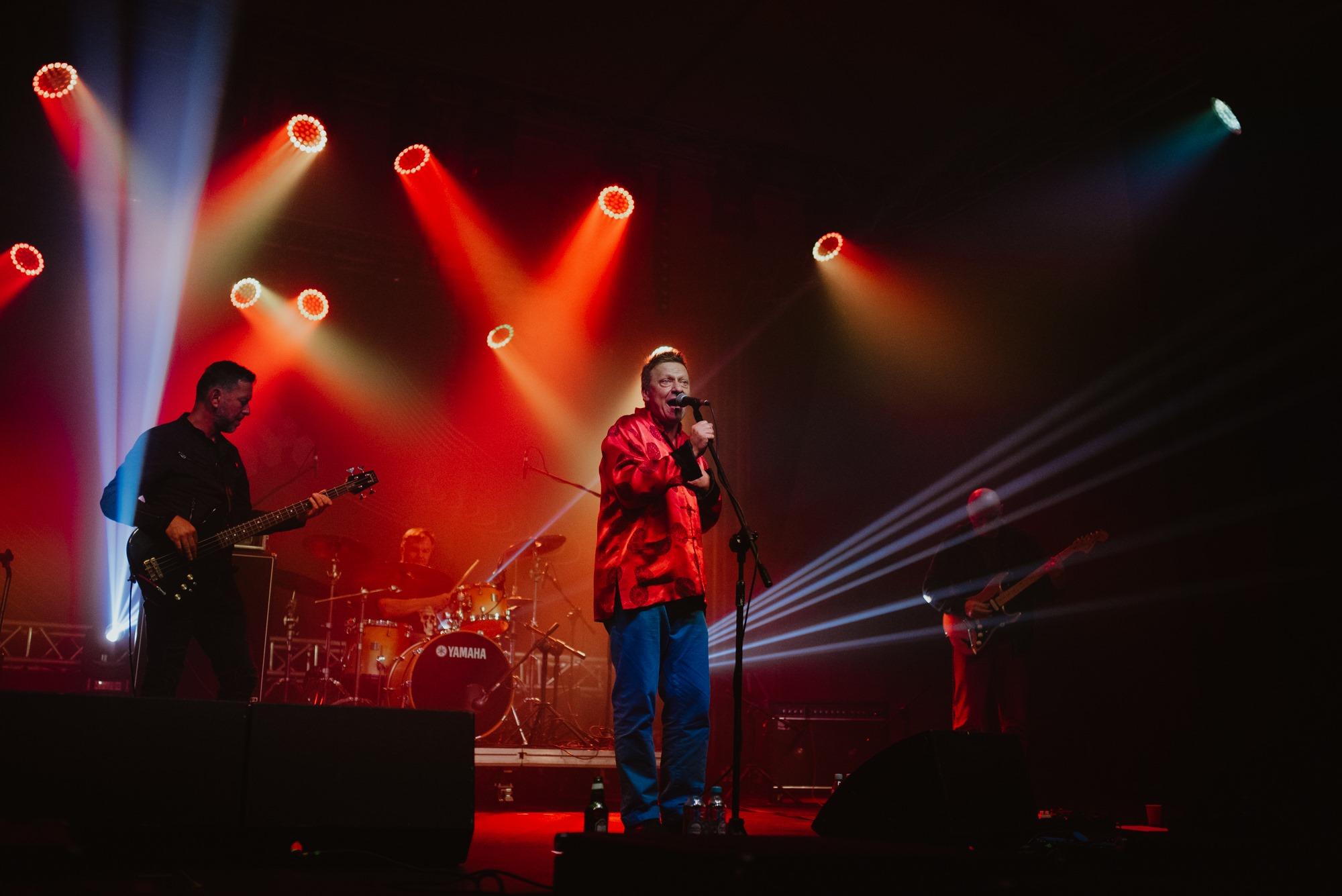 [Zdjęcie z koncertu zespołu Bielizna. Na pierwszym planie znajduje się mężczyzna w czerwonej koszuli i niebieskich spodniach śpiewający do mikrofonu. Na drugim palnie dwóch mężczyzn grających na gitarach. Na trzecim planie perkusista. Oświetlenie w kolorze czerwonym.]