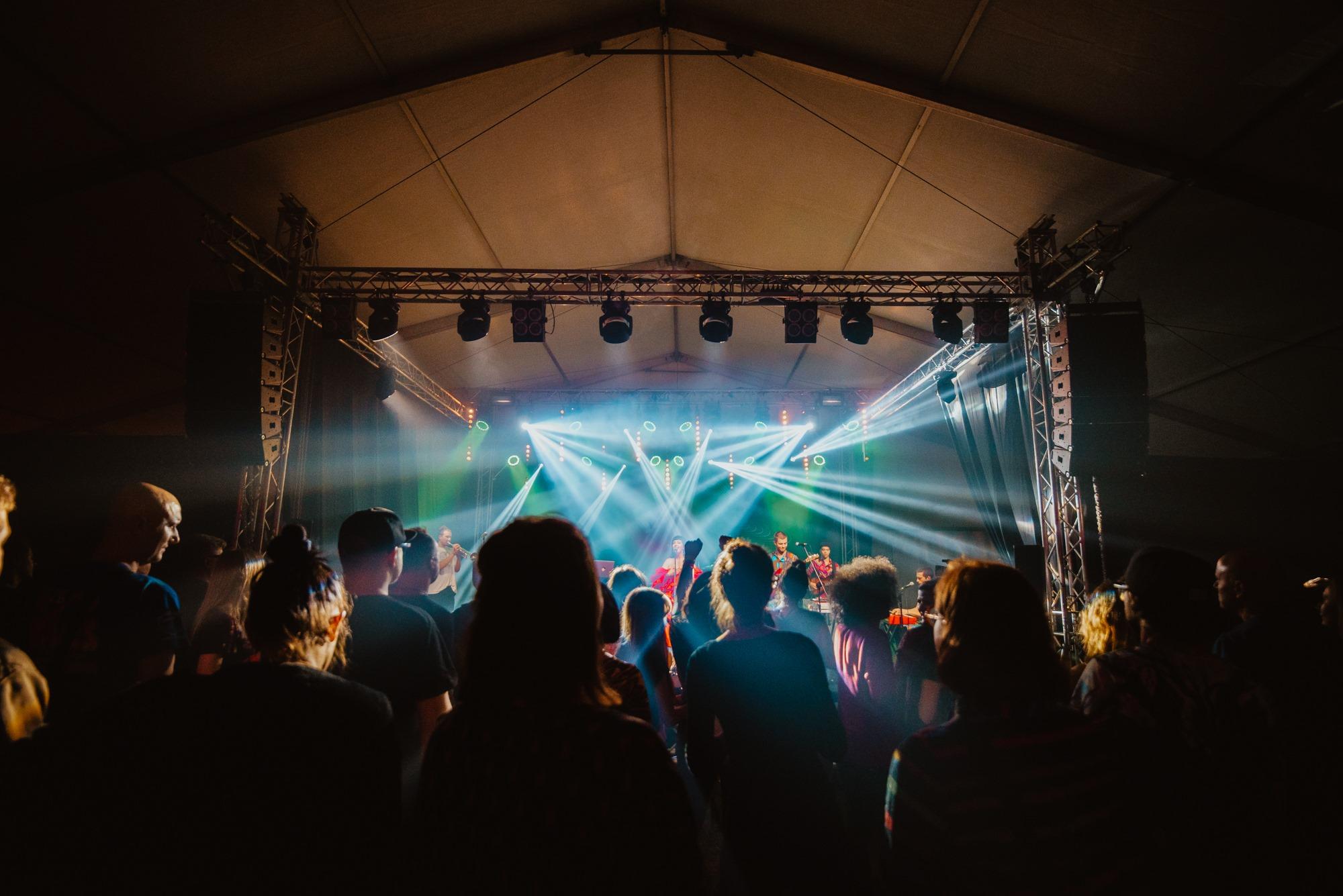 [Zdjęcie z koncertu Nubiyan Twist wykonane z perspektywy widowni. Widoczne są sylwetki osób z widowni wpatrzonych w scenę na której gra zespół. Kadr zdjęcia obejmuje całą konstrukcję sceny. Widoczna jest metalowa konstrukcja na której zamieszczone są światła oraz ogromne głośniki. Wyżej widać dach namiotu pod którym znajduje się scena.]