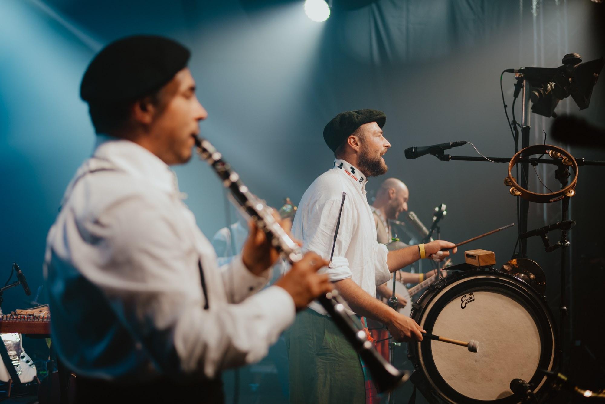 [Zdjęcie z koncertu zespołu Hańba. Mężczyźni w białych koszulach i ciemnych czapkach grający koncert na scenie. Głębia ostrości skupiona jest w centrum zdjęcia. Przedstawia mężczyznę śpiewającego do mikrofonu umieszczonego na statywie. W rękach trzyma pałeczki, którymi uderza w bębęn. Na statywie z mikrofonem zawieszony jest tamburyn. Na pierwszym planie, z lewej storny kadru, widać lekko rozmytą sylwetkę artysty grającego na klarnecie. Natomiast w tle widać rozmazaną postać bębniarza. Oświetlenie sceny jest w kolorze niebieskim.]