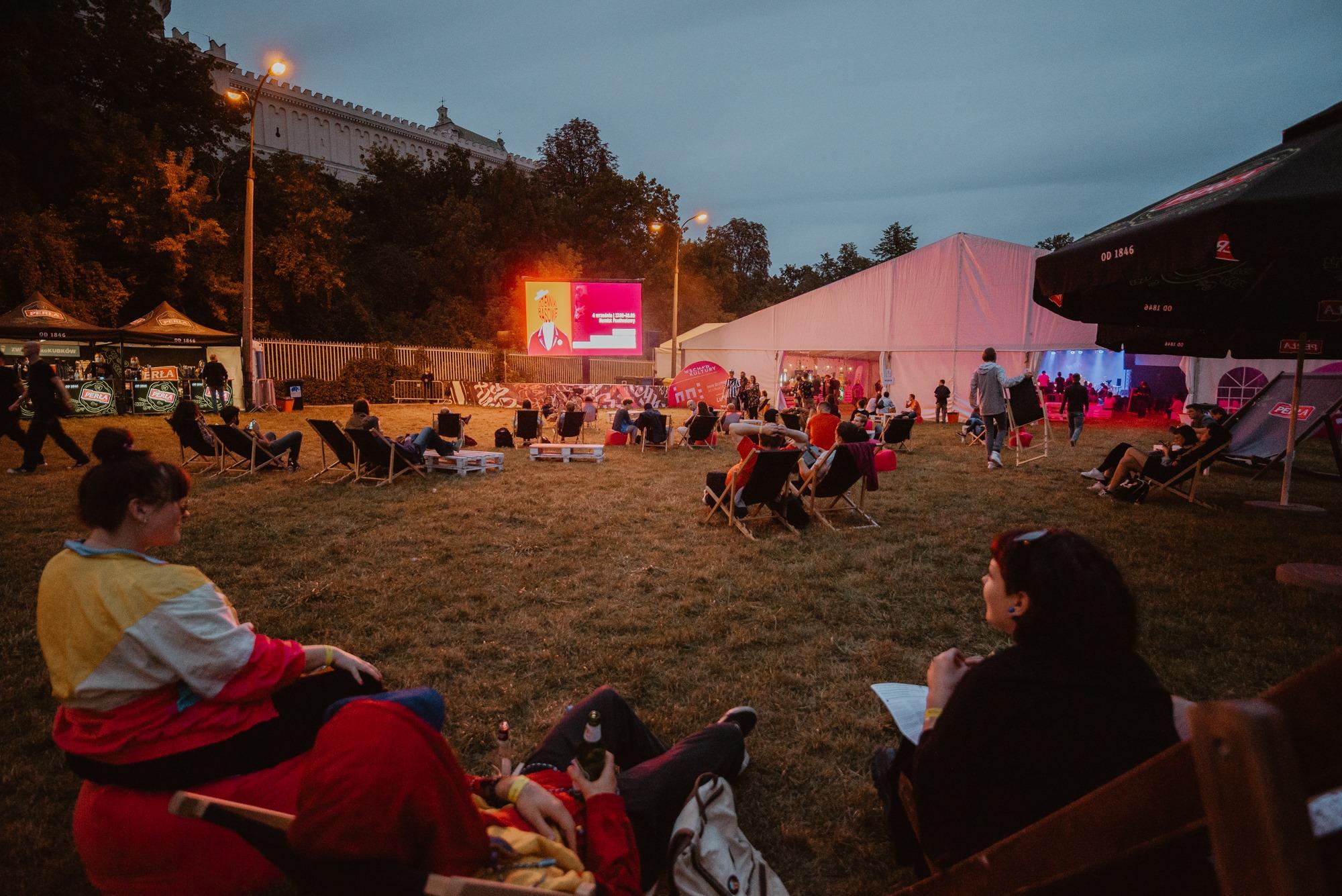 [Zdjęcie przedstawia obszar Klubu Festiwalowego. Jest to wydzielona strefa na świeżym powietrzu na Błoniach pod Zamkiem w Lublinie.  Na zdjęciu znajdują się ludzie siedzący na leżakach. Wszyscy zwróceni są w stronę ekranu, na którym wyświetlają się relacje z koncertów, które odbywają się na scenie w namiocie widocznym w tle.]