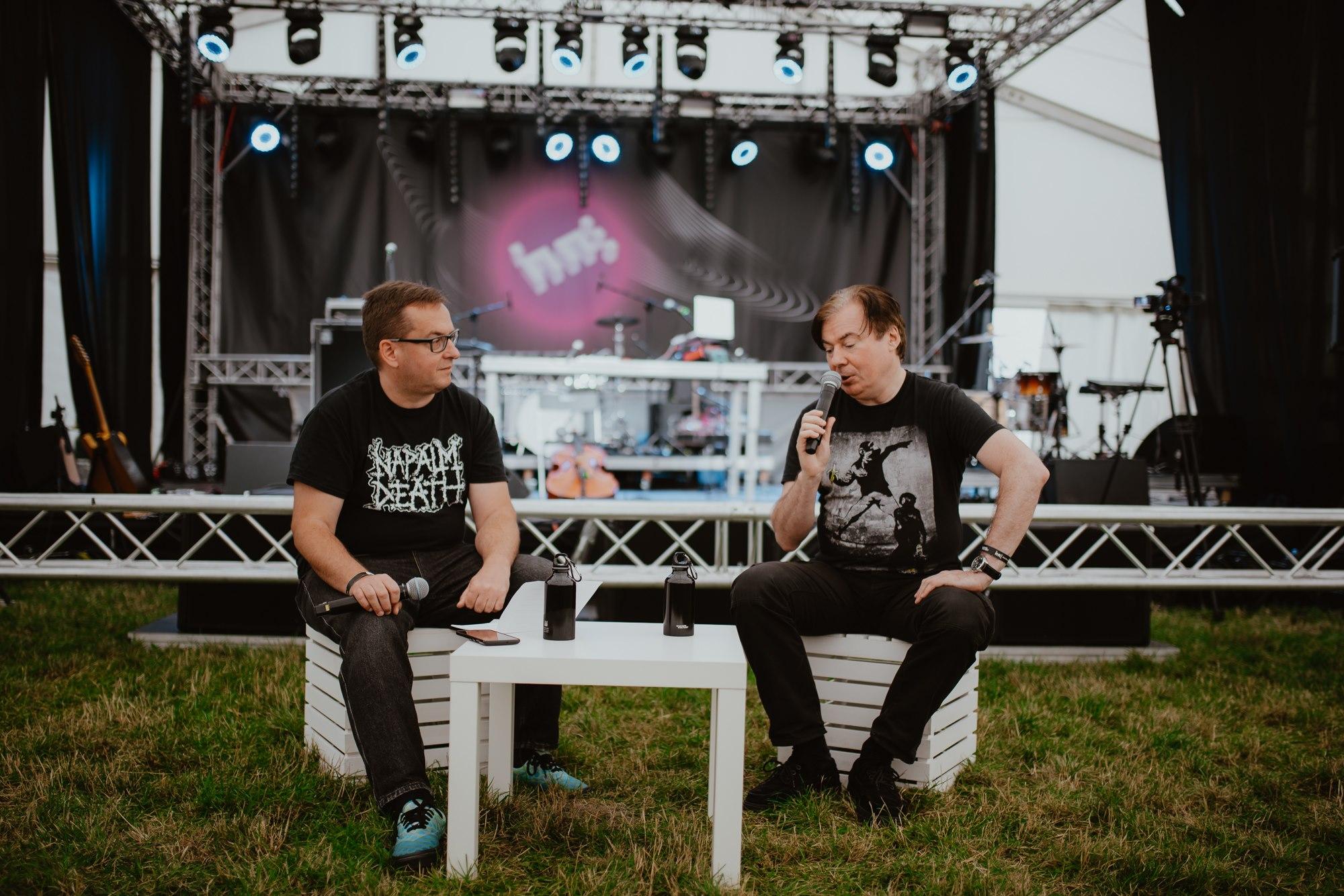 [Zdjęcie przedstawia dwóch mężczyzn siedzących na białych skrzynkach przy białym stoliku. Skrzynki są ustawione na trawie przed sceną, na której widnieje logo festiwalu Wschód Kultury  Inne Brzmienia. Na scenie widoczne są także instrumenty muzyczne oraz wysoko zawieszone światła. Jeden z mężczyzn wypowiada się do mikrofonu, drugi słucha z zainteresowaniem trzymając swój mikrofon w dłoni położonej na kolanie. Mężczyźni ubrani są w czarne koszulki z jasnymi nadrukami oraz ciemne spodnie.]
