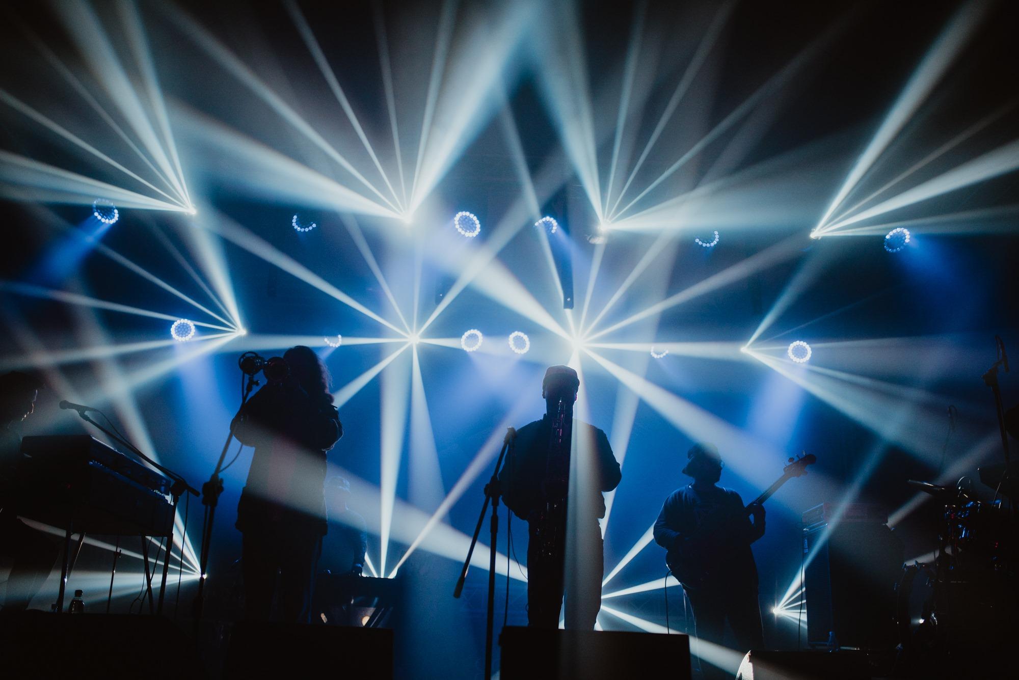 [Zdjęcie z koncertu. Widoczne są ciemne sylwetki trzech osób grających na instrumentach muzycznych. Oświetlenie nad nimi jest niebieskie rozproszone białym światłem na kształt promieni słonecznych.]