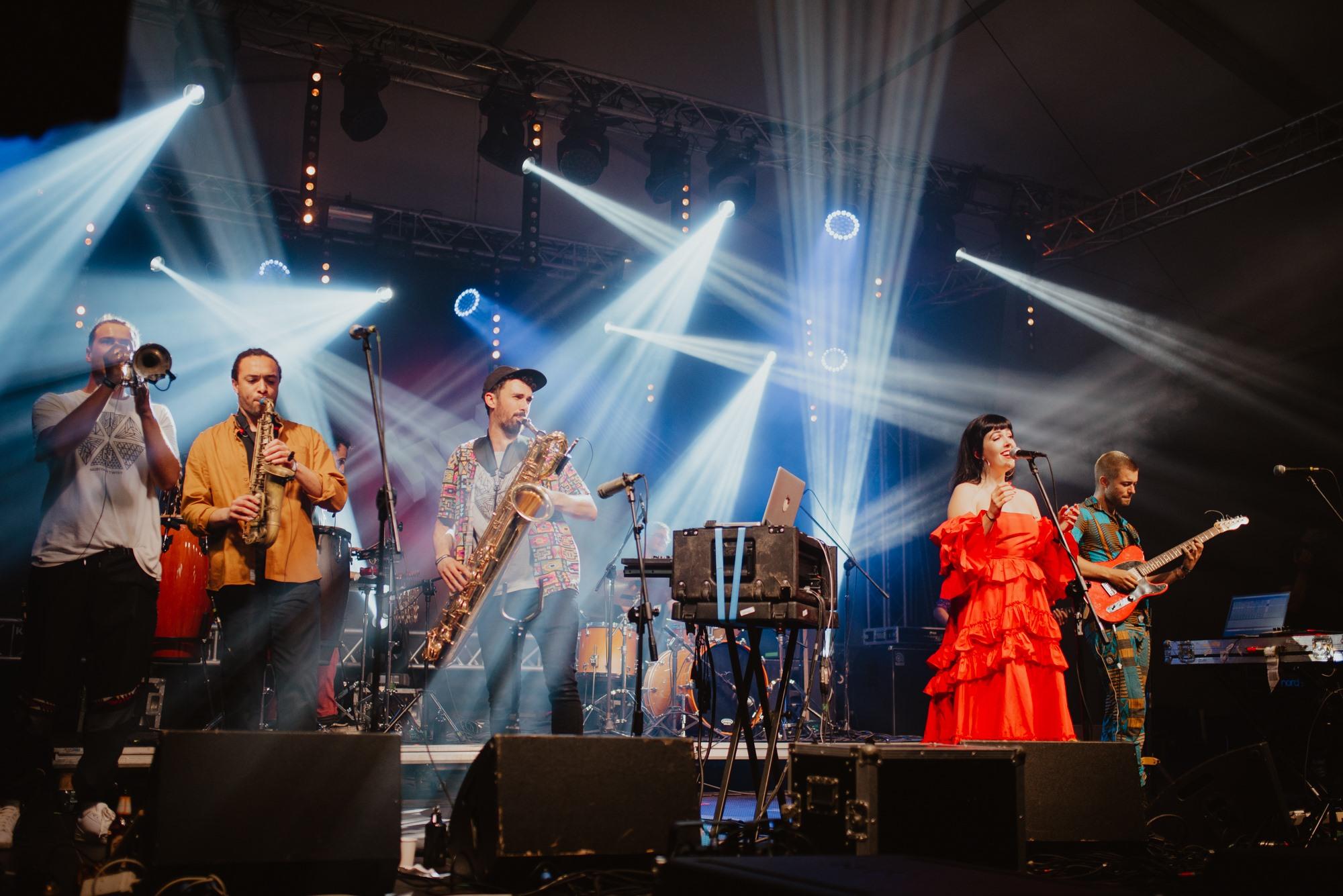 [Zdjęcie z koncertu przedstawia zespół muzyczny Nubiyan Twist na scenie. Od lewej strony - mężczyzna grający na trąbce, dwóch mężczyzn grających na saksofonach, kobieta w czerwonej sukience śpiewająca do mikrofonu oraz mężczyzna grający na gitarze.]