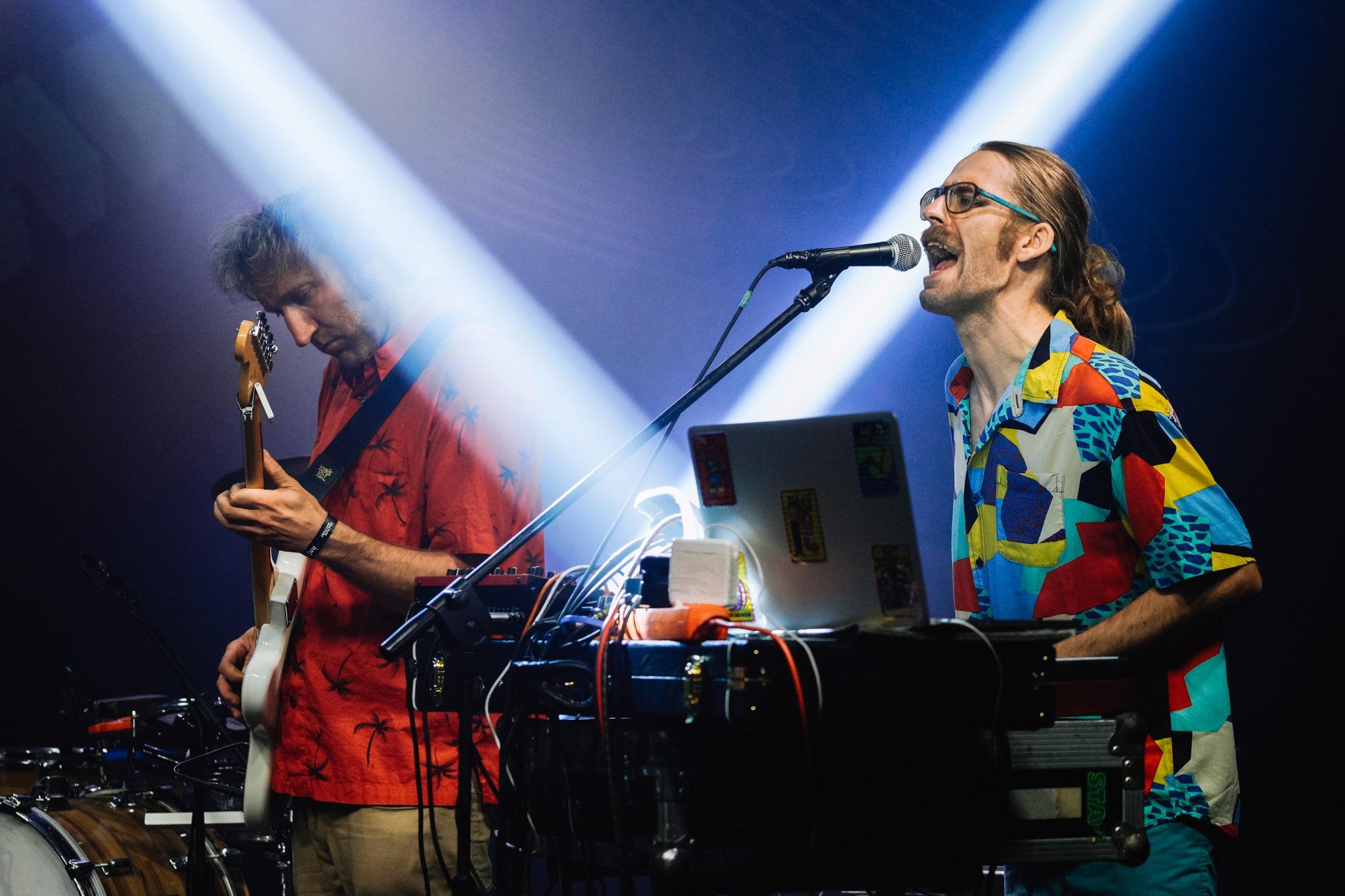 [Zdjęcie z koncertu zespołu Javva. Mężczyzna w długich, związanych włosach, okularach i kolorowej koszuli śpiewa do mikrofonu na statywie. Przed nim stoi mikser oraz otwarty laptop. Po jego prawej stronie mężczyzna ubrany w czerwoną koszulę gra na białej giarze. Panowie oświetleni są niebieskim światłem.]
