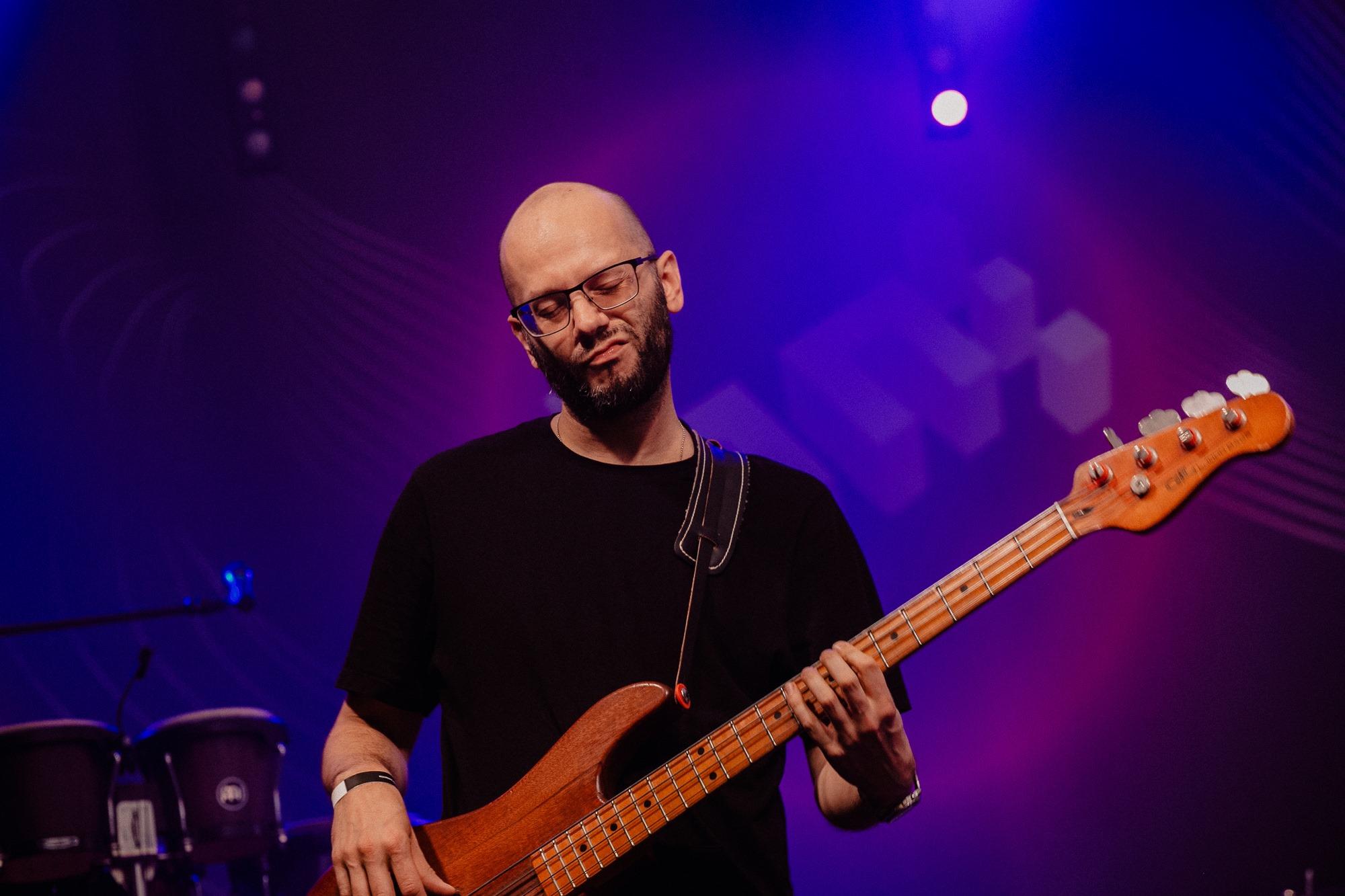 [Zdjęcie z koncertu przedstawia mężczyznę w okularach oraz w ciemnej koszulce. Mężczyzna gra na gitarze. W tle widoczne jest logo festiwalu Wschód Kultury - Inne Brzmienia. Scena oświetlona jest na niebiesko i różowo.]