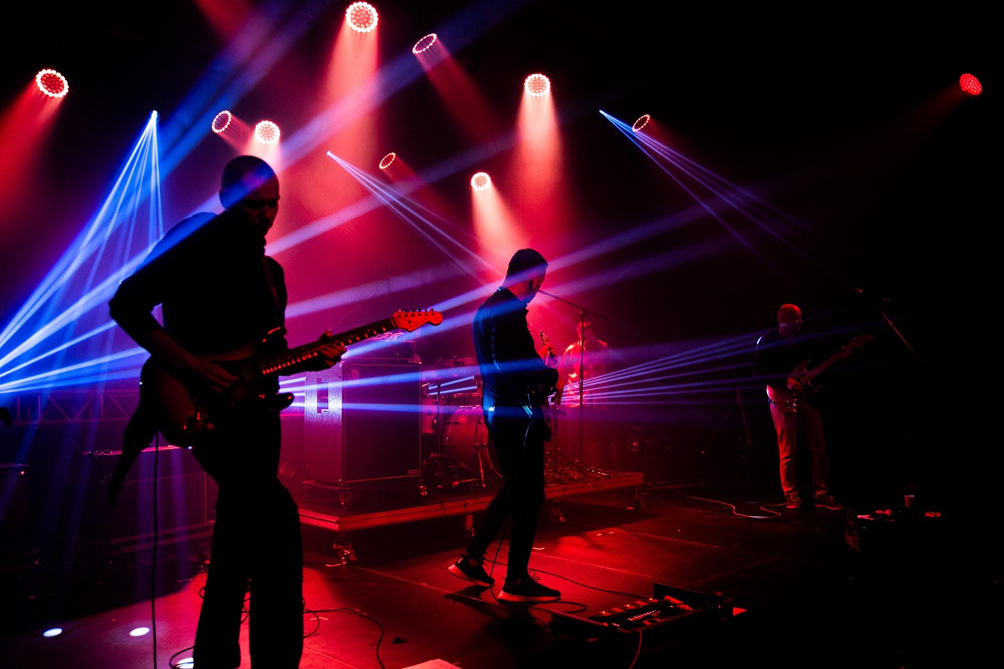 [Zdjęcie z koncertu. Trzech mężczyzn gra na gitarach. Oświetla ich czerwone światło przebijane niebieskimi promieniami światła. W tle widać perkusję i statywy z mikrofonami.]